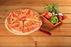 Pizza on a wooden plate Stock Image