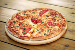 Pizza on a wooden plate Royalty Free Stock Image