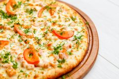 Pizza on wooden plate Stock Photo