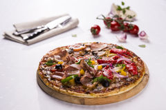 Pizza on wooden plate. Fresh pizza on a wooden plate with cutlery and ingredients stock images