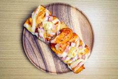 Pizza on wooden plate Stock Photos