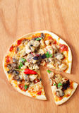 Pizza on wooden table. Delicious ready to eat crusty Italian pizza with tomato sauce, melting cheese, mushrooms, chicken, chili pepper, parsley and basil on Royalty Free Stock Image