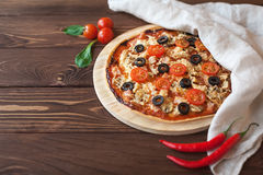 Pizza on wooden table. Italian pizza on wooden table royalty free stock image