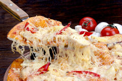 Pizza on a wooden table at which raise the class with stringy cheese Royalty Free Stock Photos