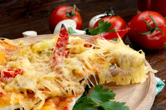 Pizza on a wooden table at which raise the class with stringy cheese Royalty Free Stock Photo