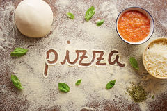 Pizza word written on table. Composition with ingredients stock image