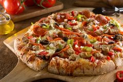 Pizza With the Works. A delicious pizza with pepperoni, sausage, black olives, red pepper, green pepper, and onions Royalty Free Stock Images