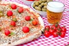 Pizza y cerveza en la tabla - comida deliciosa Fotos de archivo libres de regalías