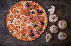 Pizza y diversos ingredientes en ella Fondo oscuro Visión desde arriba fotografía de archivo libre de regalías