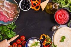 Pizza y fondo de los ingredientes Foto de archivo libre de regalías