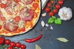 Pizza y verduras en una tabla de madera oscura imagenes de archivo