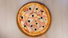 Pizza z baleronem i serem na drewnianej desce na stole blisko lily farbuje mi?kki na widok wody zbiory