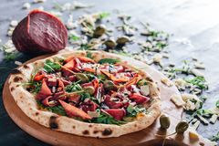 Pizza z baleronem, rakietową sałatką, kaparem i parmesan, zdjęcia stock