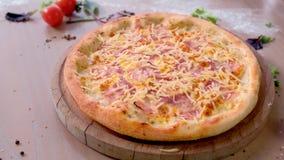 Pizza z bekonem i serem na drewnianej desce na stole zako?czenie boczny widok zbiory