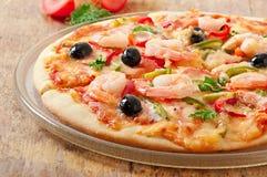 Pizza z garnelą, łososiem i oliwkami, Fotografia Stock