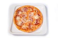 Pizza z kiełbasą i serem w białym talerzu na odosobnionym białym tle obrazy stock