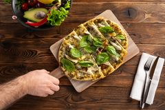 Pizza z kurczakiem, pieczarki, ser i ręka mężczyzna który trzyma deskę, obrazy royalty free