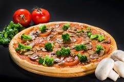 Pizza z mozzarellą, pieczarką, brokułami, cebulą i pomidorami, dalej obrazy royalty free