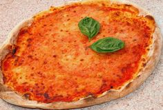 Pizza z mozzarellą, pomidor i dwa basilów liście w Ita Zdjęcie Royalty Free