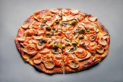 Pizza z pieczarkami, oliwkami, mozzarellą, pomidorami i kiełbasami na czarnym tle, Obraz Stock