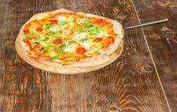 Pizza z pizzy szpachelką na starym drewnianym stole Fotografia Royalty Free