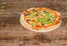 Pizza z pizzy szpachelką na starym drewnianym stole Zdjęcia Royalty Free