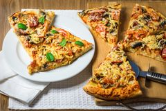 Pizza z pomidorami, serem i pieczarkami na stole, zdjęcie royalty free