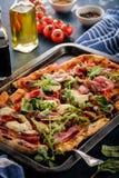 Pizza z prosciutto, mozzarelli, pieczarkowej i rakietowej sałatki dowcipem, fotografia stock