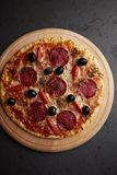Pizza z salami, mozzarella serem, czereśniowymi pomidorami, czarnymi oliwkami i oregano, Dom zrobił jedzeniu Pojęcie dla serdeczn obraz royalty free