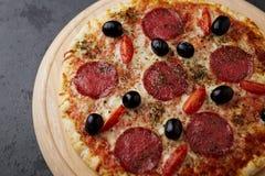 Pizza z salami, mozzarella serem, czereśniowymi pomidorami, czarnymi oliwkami i oregano, Dom zrobił jedzeniu Pojęcie dla serdeczn fotografia stock