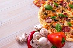 Pizza z salami pikantność na białym drewnianym tle z kopii przestrzenią i warzywami Zdjęcie Stock