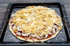 Pizza zugebereitet, um zu backen stockbilder