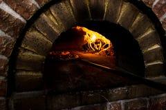 Pizza zwei in einem hölzernen brennenden Ofen Lizenzfreie Stockbilder