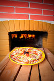 Pizzabacken mit hölzernem Feuer Stockbild