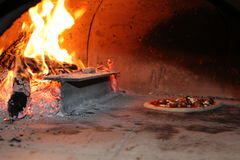Pizzabakning i den wood ugnen Royaltyfri Foto