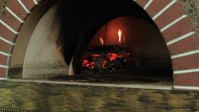 Pizzabakning i en trä avfyrad ugn stock video
