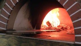 Pizzabakning i en trä avfyrad ugn arkivfilmer