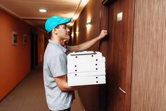 Pizzabote, der auf Tür des Kunden klopft lizenzfreie stockfotos