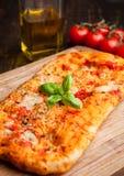 Pizzabrot mit Tomaten und Olivenöl auf hölzernem Brett Stockbilder