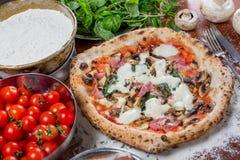Pizzacapricciosa med kronärtskockan, skinka och champinjonen på wood backg Royaltyfria Bilder