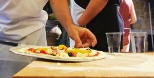 Pizzadanande i matlagninggrupp Arkivfoto