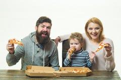 Pizzafamilie Mutter, Vater und Kind, ein kleiner Sohn mit den Eltern, die Pizza essen Familienabendessen mit Mutter und Vati ital lizenzfreie stockfotografie