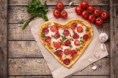 Pizzahjärta som formas med peperonin, tomater royaltyfria bilder
