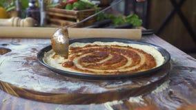 Pizzaillo che cucina pizza con la pasta del pomodoro in pizzeria italiana Cuoco del cuoco unico che cucina preparando pizza sulla stock footage