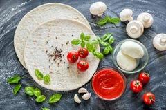 Pizzaingredienser på den mörka träbakgrunden Fotografering för Bildbyråer