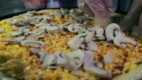 Pizzaiolo pouring mushrooms on pizza stock video footage