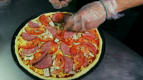 Pizzaiolo pouring salami on pizza stock video footage