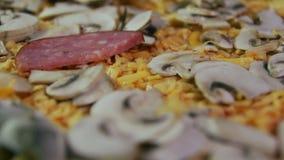 Pizzaiolo pouring salami on pizza stock video