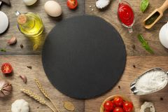 Pizzalebensmittelinhaltsstoffe und Schieferstein stockfotografie