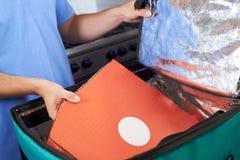 PizzaleveransPerson Putting Food Into Insulated påse i Restaur royaltyfri fotografi